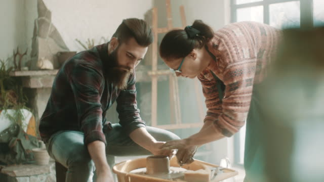 Senior woman teaching young man how to use pottery wheel