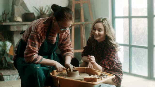 senior woman teaching young woman how to use pottery wheel - art and craft stock videos & royalty-free footage