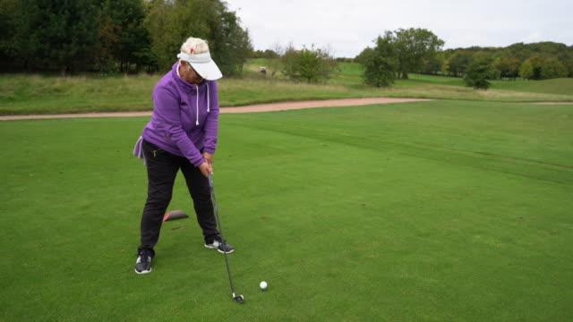 a senior woman teeing off - sonnenschild stock-videos und b-roll-filmmaterial