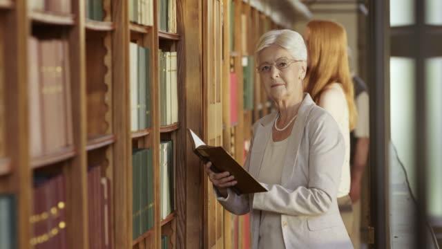 TU Senior vrouw thumbing door middel van een boek over bibliotheek balkon