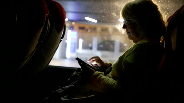 Senior woman traveling by bus and using her smartphone