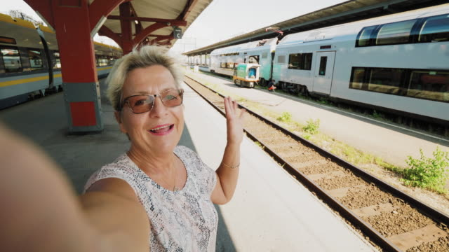 A senior woman traveling by train is taking a selfie