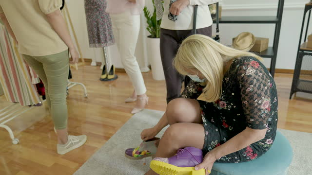 vídeos de stock e filmes b-roll de senior woman trying on shoes in female fashion shop - viciado em compras
