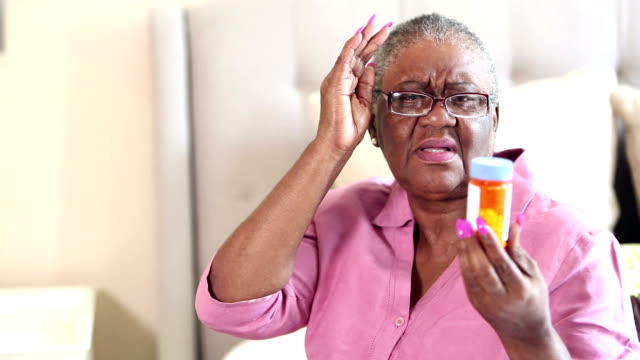 senior woman trying to read prescription medicine bottle - prescription medicine home stock videos & royalty-free footage