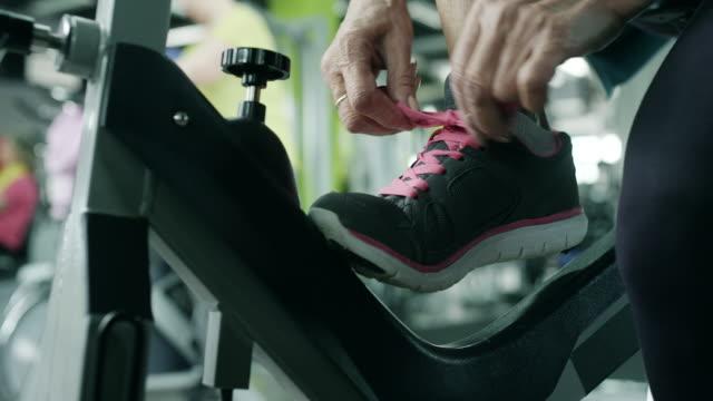 senior woman tying shoelaces - exercise bike stock videos & royalty-free footage