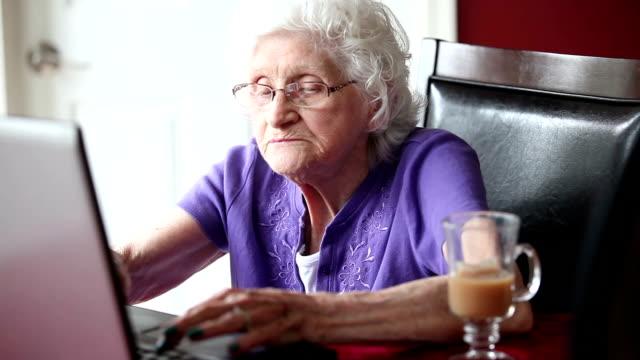 vídeos de stock e filmes b-roll de senior woman typing on laptop - centenário