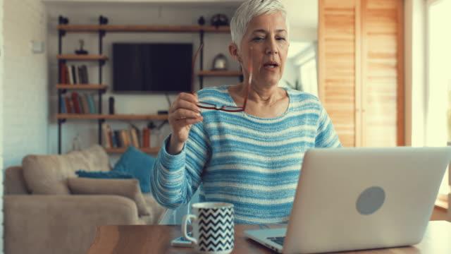 stockvideo's en b-roll-footage met senior vrouw typen op laptop tijdens het schrijven van een e-mail thuis. - e mail