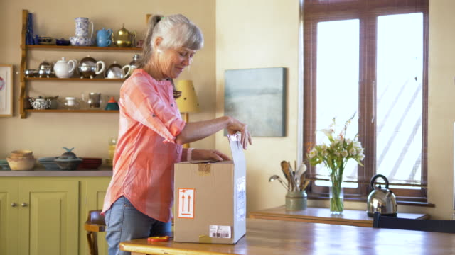 vídeos de stock, filmes e b-roll de senior woman unpacking a package from an online purchase - desempacotando