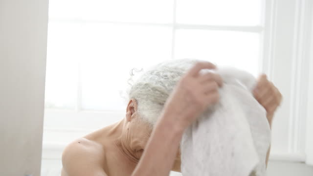 senior woman unwrapping wet hair in towel - wet hair stock videos & royalty-free footage