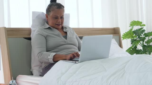 vídeos de stock, filmes e b-roll de mulher idosa usar laptop no quarto - idoso na internet