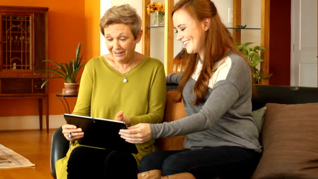 senior woman uses digital tablet with daughter - tongue tied stock videos and b-roll footage