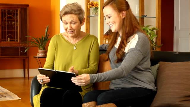 stockvideo's en b-roll-footage met senior vrouw maakt gebruik van digitale tablet met dochter - communication problems