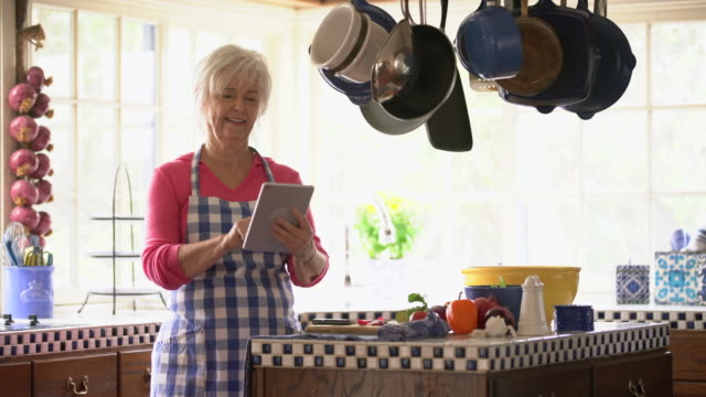 ms senior woman using a digital tablet while cooking - arbeitsplatte stock-videos und b-roll-filmmaterial