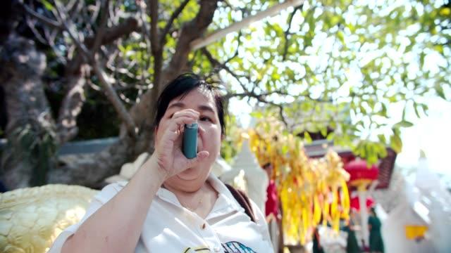 vidéos et rushes de haute femme utilisant l'asthme inhalateur - inhalateur