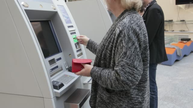 senior woman using atm, handheld shot - inserting stock videos and b-roll footage