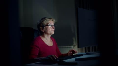 senior kvinna med hjälp av dator - journalist bildbanksvideor och videomaterial från bakom kulisserna