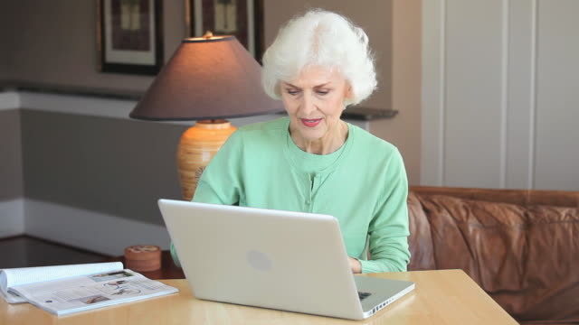 ms senior woman using credit card to shop online with laptop, eastville, virginia, usa - home shopping stock videos & royalty-free footage