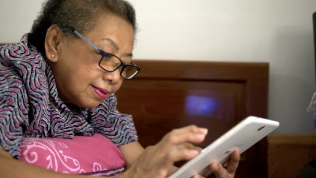 senior woman using digital tablet 4k - silver surfer stock videos & royalty-free footage