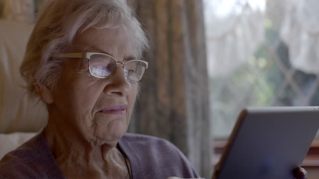 senior woman using digital tablet at home. - only senior women stock videos & royalty-free footage