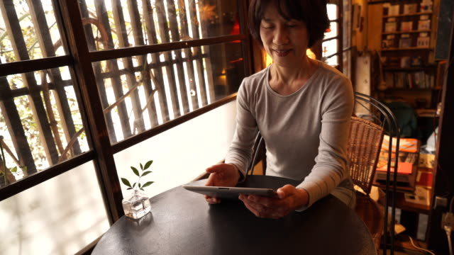 Senior woman using digital tablet in a cafe