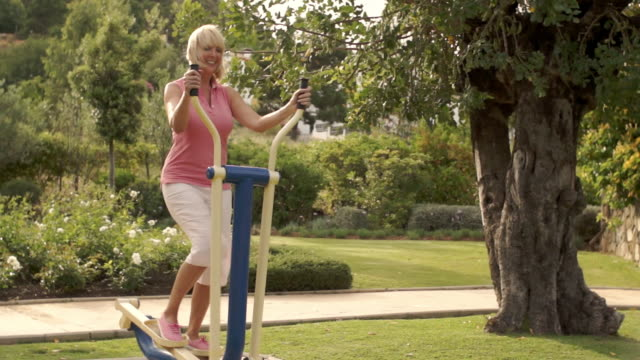 senior woman using exercise machine in park. - 55 59 jahre stock-videos und b-roll-filmmaterial