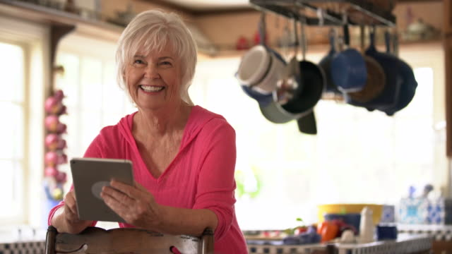 ms senior woman using her digital tablet in the kitchen - donne anziane video stock e b–roll