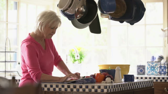 MS Senior woman using her digital tablet in the kitchen