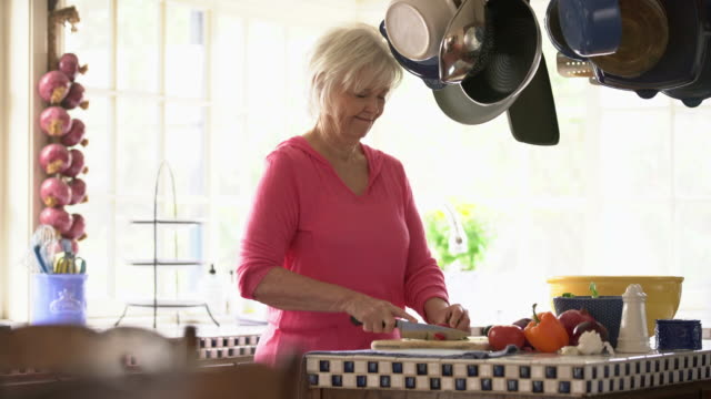 ms senior woman using her digital tablet while cooking - arbeitsplatte stock-videos und b-roll-filmmaterial