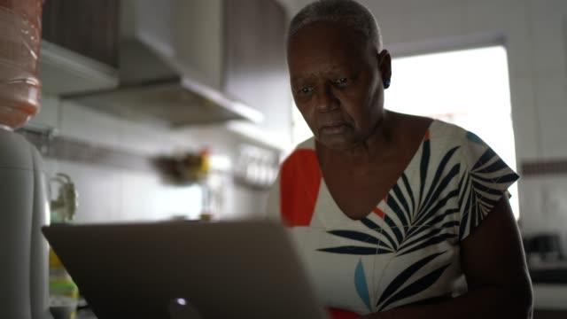 vídeos de stock, filmes e b-roll de idosa usando laptop em casa - e commerce