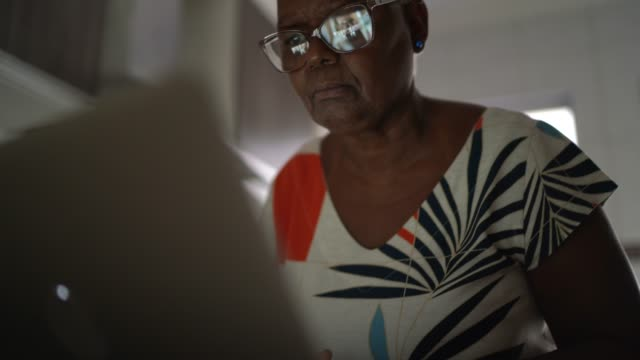senior woman using laptop at home - gender stereotypes stock videos & royalty-free footage