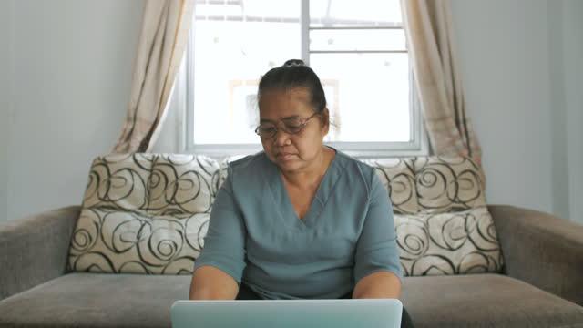 senior kvinna som använder bärbar dator hemma - människofinger bildbanksvideor och videomaterial från bakom kulisserna