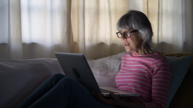 senior woman using laptop computer to speak to friends from home - weinglas stock-videos und b-roll-filmmaterial
