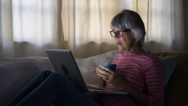 vídeos de stock, filmes e b-roll de senior woman using laptop computer to speak to friends from home - idoso na internet