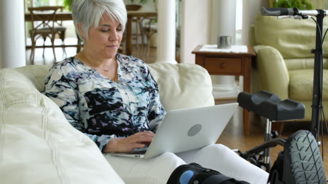 stockvideo's en b-roll-footage met senior woman using laptop while sitting on a couch - oudere internetgebruiker