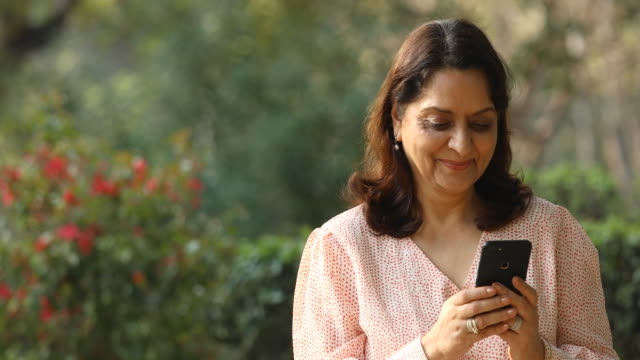 senior woman using mobile phone at park - indian ethnicity stock videos & royalty-free footage