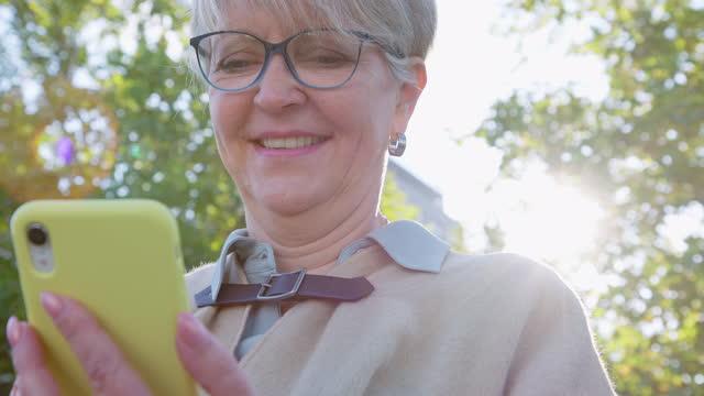 senior woman using mobile phone outdoors - grey hair stock videos & royalty-free footage