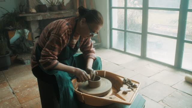 芸術的なアトリエで陶器のホイールを使用して年配の女性 - 陶芸家点の映像素材/bロール