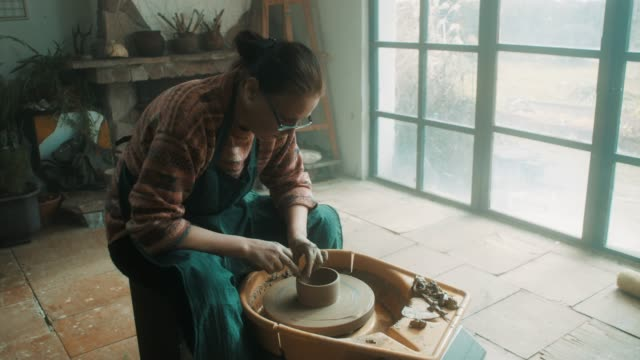 Senior woman using pottery wheel at artistic atelier