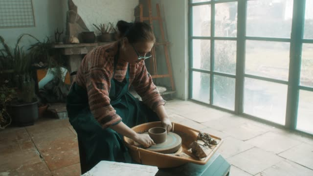senior woman using pottery wheel at artistic atelier - hobby video stock e b–roll