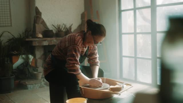 Senior woman using pottery wheel at atelier
