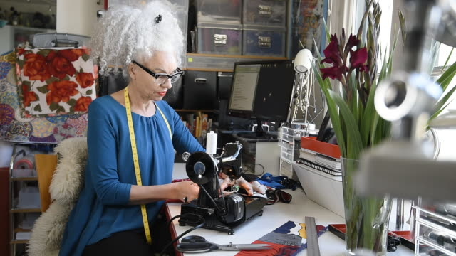 senior woman using sewing machine in office - artisan stock videos and b-roll footage