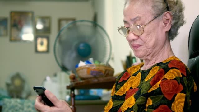 vidéos et rushes de femme senior avec téléphone intelligent à la maison - seniornaute