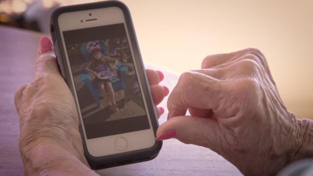 vidéos et rushes de senior woman using smart phone - photo messaging