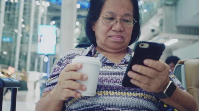 senior woman using smartphone at airport - biglietto aereo video stock e b–roll