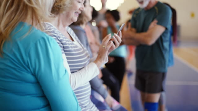 Senior woman using smartphone while waiting her dance class to begin