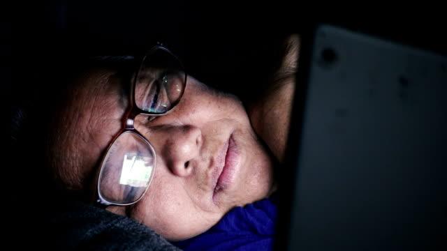 Senior woman using tablet computer on the sofa at night
