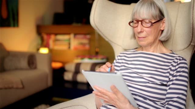 senior frau mit tablet-computer - standbildaufnahme stock-videos und b-roll-filmmaterial