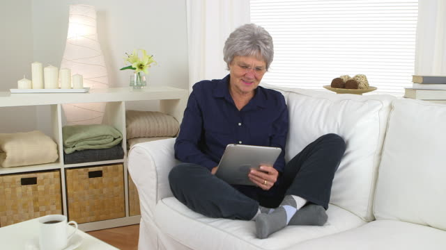 stockvideo's en b-roll-footage met senior woman using tablet on couch - oudere internetgebruiker