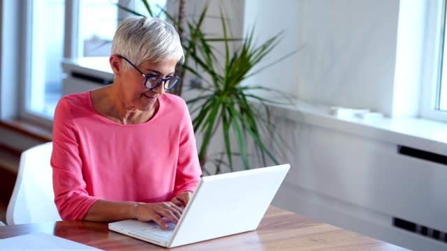 Senior woman using technology to keep in touch with her family