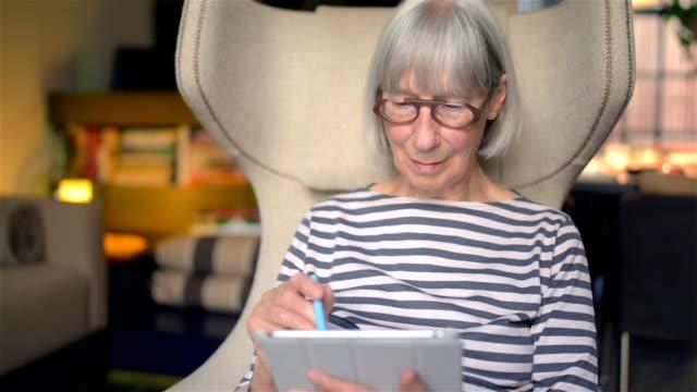 vidéos et rushes de senior femme en utilisant la technologie - seniornaute